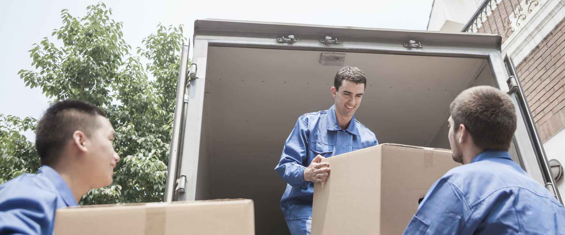 bigstock-Movers-unloading-a-moving-van-52631176-1920x800